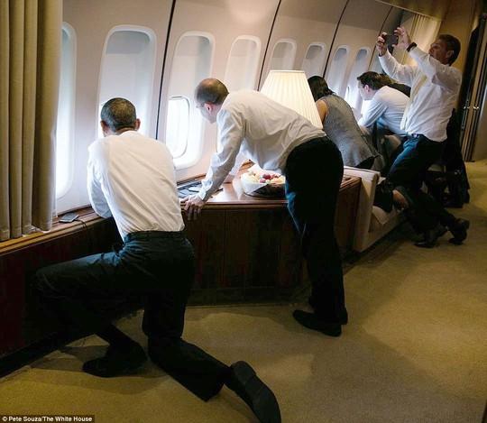 Các nhân viên Nhà Trắng chăm chú nhìn ra ngoài cửa sổ trên chiếc chuyên cơ Air Force 1. Ảnh: White House