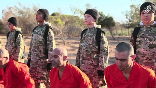 Cậu bé người Anh (thứ hai từ phải sang) không cho thấy dấu hiệu bị tẩy não. Ảnh: Daily Mail