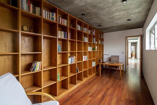 Phòng làm việc với kệ gỗ ốp tường gọn gàng.