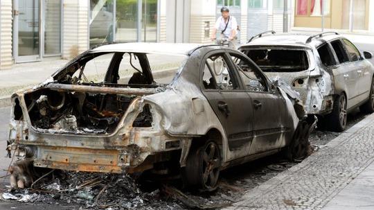 Xe cảnh sát bị đốt cháy. Ảnh: AP