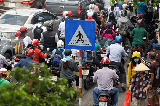 Người đi bộ phải chen nhau với dòng xe máy leo lề