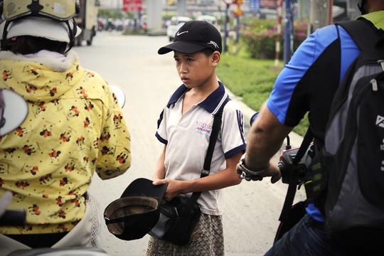 Tại nút đèn đỏ trên xa lộ Hà Nội đoạn hướng từ cầu Rạch Chiếc lên cầu vượt Cát Lái thường xuất hiện một em nhỏxin tiền người đi đường.