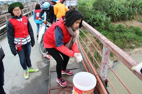 Nhiều tình nguyện viên đứng dọc hai bên cầu giúp người dân thả cá xuống sông, cũng như nhắc nhở mọi người không thả túi nilon