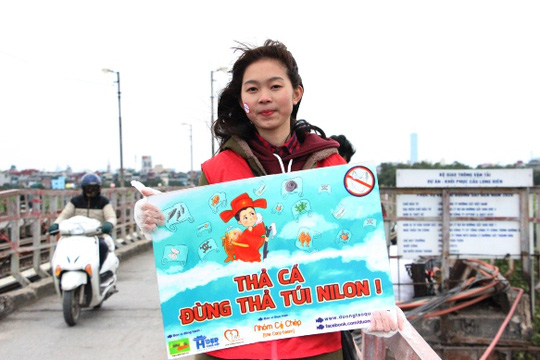 Một bạn sinh viên trong nhóm tình nguyện cầm tấm biển Thả cá đừng thả túi nilon