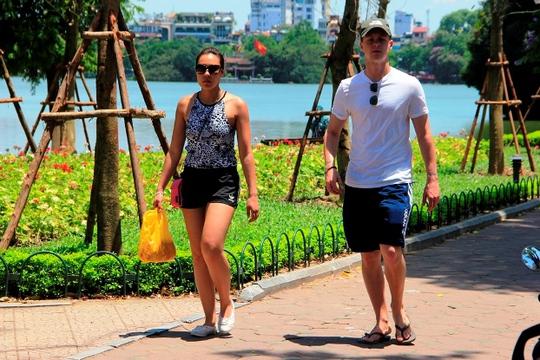 Du khách nước ngoài thưởng thức nắng nóng bên Hồ Gươm