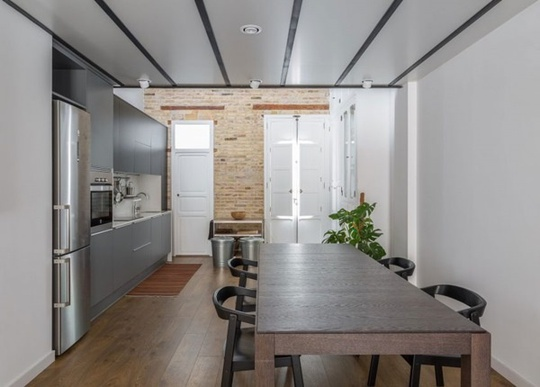 Sự hài hòa giữa vật liệu thân thiện với môi trường của bộ bàn ghế ăn với vật liệu hiện đại của hệ thống tủ và đồ dùng nấu ăn màu ghi xám mang lại vẻ đẹp cuốn hút và hài hòa cho gian bếp nhỏ