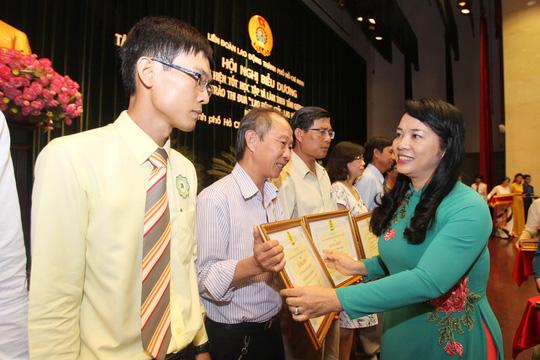 Bà Trần Kim Yến, Chủ tịch LĐLĐ TP HCM, trao bằng khen cho các tập thể điển hình trong phong trào học tập và làm theo tấm gương đạo đức Bác Hồ Ảnh: HOÀNG TRIỀU