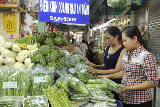 Chị Nguyễn Thị Huyền Trân (bìa phải) kiểm tra một điểm kinh doanh rau sạch
