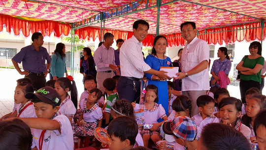 Đại diện Trung tâm Công tác xã hội Công đoàn và Bưu điện Chợ Lớn trao thẻ BHYT cho Trường Tiểu học Hòa Hiệp, huyện Cần Giờ, TP HCM