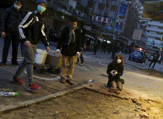 Người biểu tình cạy gạch ở vỉa hè ném cảnh sát. Ảnh: Reuters