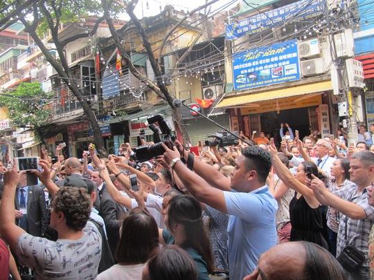 Người dân hò reo và giơ máy ảnh, điện thoại chụp hình khi Tổng thống ra khỏi quán