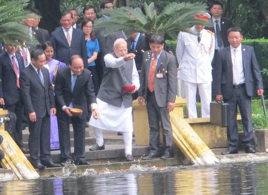 Hai Thủ tướng cùng cho cá trong Ao cá Bác Hồ ăn