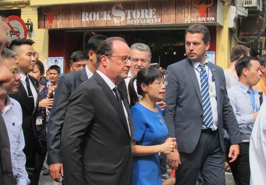 Tổng thống vừa tản bộ trên phố vừa nghe một hướng dẫn viên giới thiệu về phố cổ Hà Nội