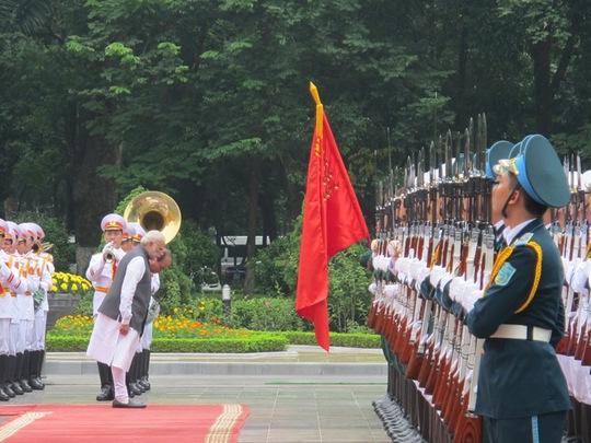 Hai Thủ tướng cúi chào Quốc kỳ Việt Nam trước khi duyệt đội danh dự Quân đội nhân dân Việt Nam