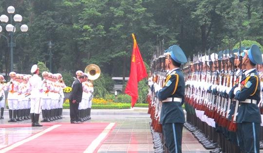 Tổng thống và Chủ tịch nước cúi chào quốc kỳ trước khi duyệt đội danh dự