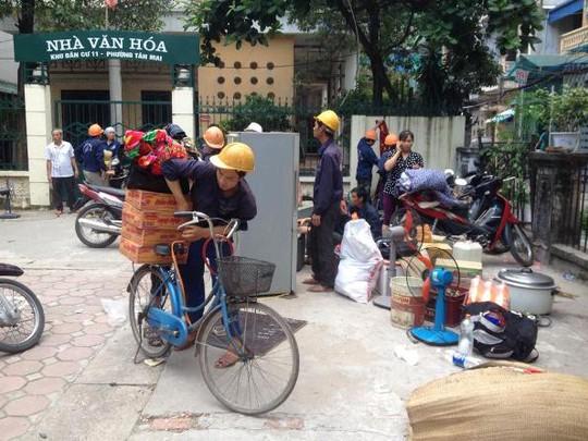 Người dân thu dọn đồ đạc đã sơ tán ra ngoài hiện trường vụ cháy