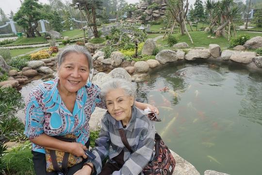 NSƯT Lê Thiện và Út Bạch Lan chụp ảnh tại hồ cá trong khuôn viên Đền thờ Tổ của NSƯT Hoài Linh