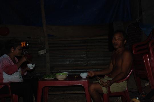 Suốt 20 năm qua, vợ chồng bà Sơn Thị Sa Nương vẫn phải ăn cơm tối với chiếc đèn pin treo trên đầu