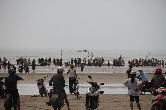 Rất đông người dân tập trung trên bãi biển nơi phát hiện cá voi chết.