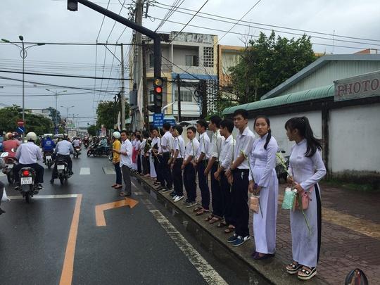 Các em học sinh với cành huệ trắng trên tay ngậm ngùi tiễn đưa gia đình thầy giáo Tiên