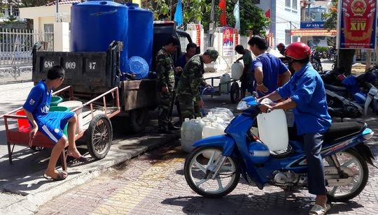 Nhiều người tranh thủ mang can nhựa đến nhận những giọt nước nghĩa tình của gia đình ông Sáu với sự hỗ trợ của lực lượng làm nhiệm vụ.