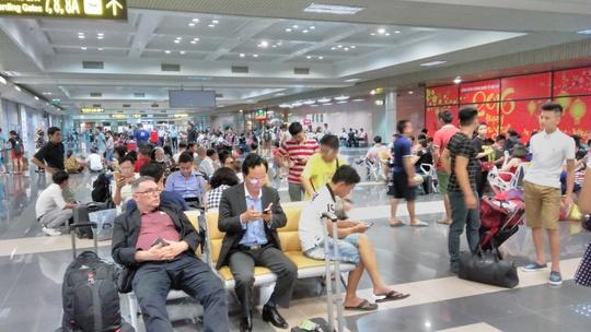Hành khách chờ làm thủ tục tại sân bay Nội bài sau khi bị sự cố tấn công mạngẢnh: HẢI LINH