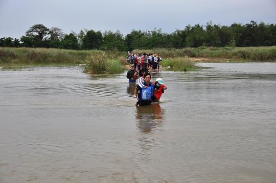 Nước sông Trà Khúc dâng cao, người dân phải cõng con em qua đoạn đường bị nước sông ngập. Ảnh: Tử Trực