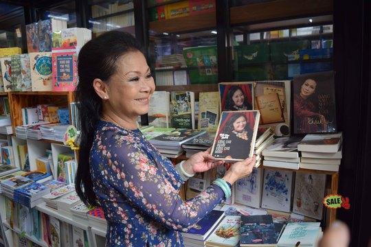 Nữ danh ca trước giá sách có những cuốn hồi ký ghi lại cuộc đời bà, Khánh Ly chọn hồi ký của kỳ nữ Kim Cương ngay cạnh đó.