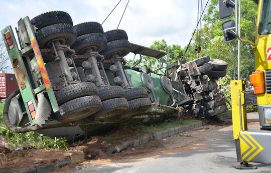 Phần bồn xe gãy rời nằm trên vệ đường đang được xe cẩu giải cứu.