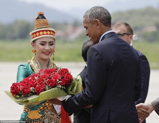 Tổng thống Mỹ được tặng hoa chào đón khi đáp xuống sân bay Luang Prabang. Ảnh: AP