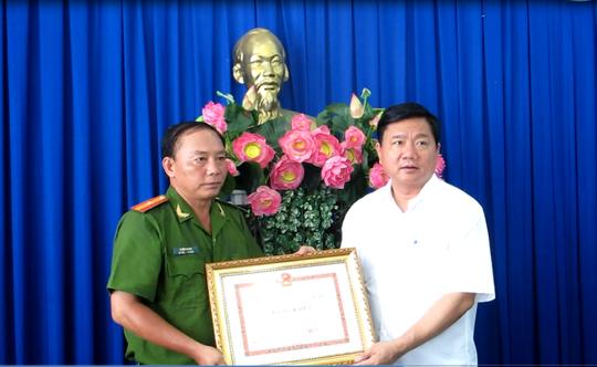 Bí thư Thành ủy Đinh La Thăng thay mặt lãnh đạo TP tặng bằng khen cho Công an quận 8. Ảnh: PHẠM DŨNG