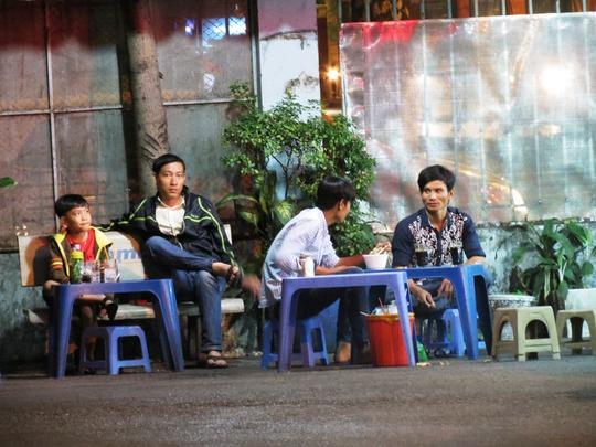 12 giờ đêm, ngoài sân BV vẫn rải rác nhiều người đàn ông ngồi uống nước hay ăn đêm bằng tô mì gói để chờ đợi người thân...