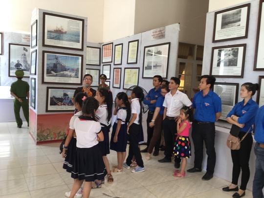 Các học sinh chăm chú lắng nghe thuyết trình về các tư liệu tại triển lãm
