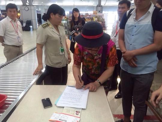 Bà Yan Fengge ký vào biên bản vì hành vi trộm cắp của mình - ảnh: ANHK