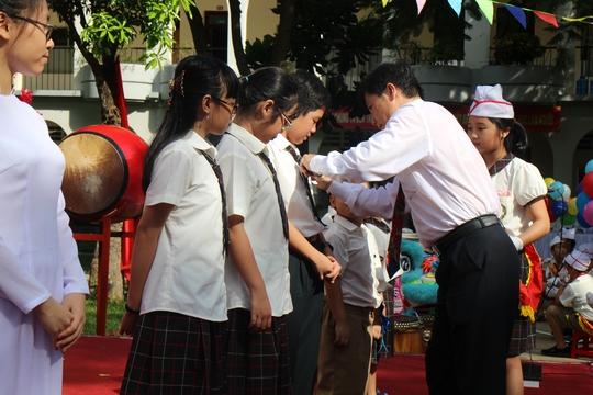 Thầy hiệu trưởng gắn huy hiệu trường cho học sinh đầu cấp