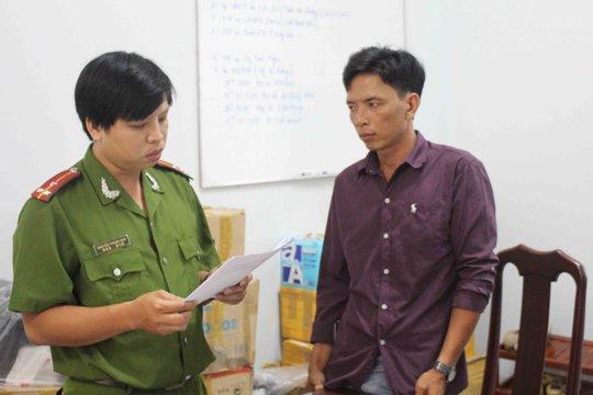 Bị can Giàu (bên phải) đang nghe cán bộ điều tra Công an quận Ninh Kiều đọc quyết định khởi tố bị can