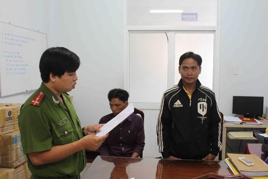 Bị can Đoàn (phải) đang nghe đọc quyết định khởi tố bị can và cấm đi khỏi nơi cư trú