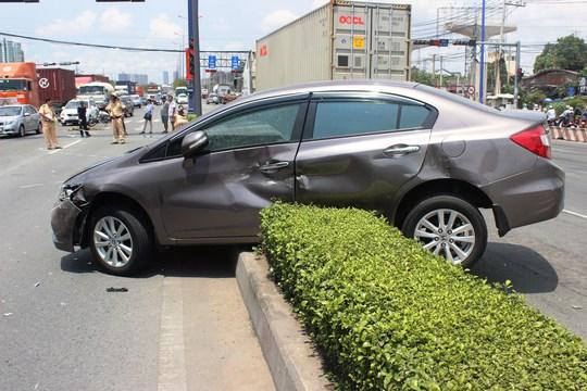 Chiếc ô tô 4 chỗ nằm vắt vẻo trên dải phân cách