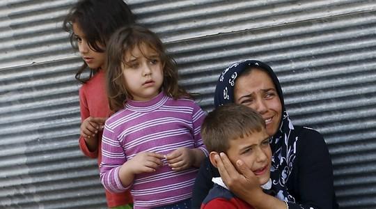Bốn mẹ con bàng hoàng sau vụ tấn công bằng rocket thị trấn Kilis của Thổ Nhĩ Kỳ ngày 24-4. Ảnh: REUTERS
