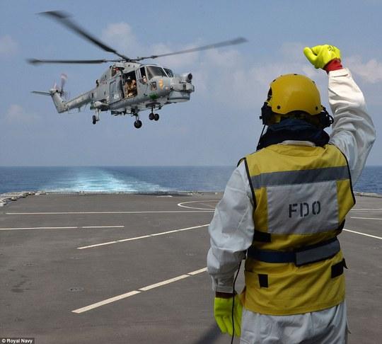 Một binh lính vẫy tay chào tạm biệt máy bay trực thăng khi tàu khu trục HMS Defender của Hải quân Hoàng gia Anh huấn luyện hồi tháng 1. Ảnh: Hải quân Hoàng gia Anh