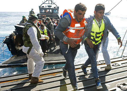 Người di cư từ một chiếc thuyền gỗ lên tàu chiến HMS Bulwark. Chiếc HMS Bulwark có nhiệm vụ cứu hộ 5.000 di dân từ châu Phi. Ảnh: Hải quân Hoàng gia Anh
