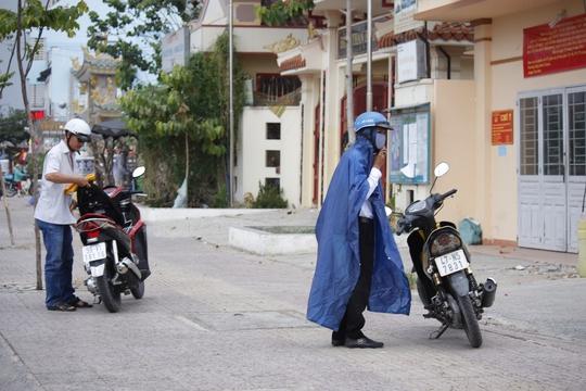 Trên đường Phạm Văn Đồng, nhiều người dân vội vàng mang áo mưa đã chuẩn bị sẵn trước khi cơn mưa ập tới.
