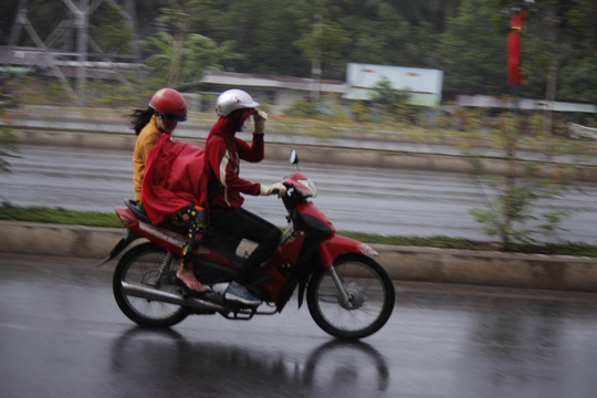 Người lớn chịu ướt mưa để dành áo mưa che chắn cho trẻ nhỏ.
