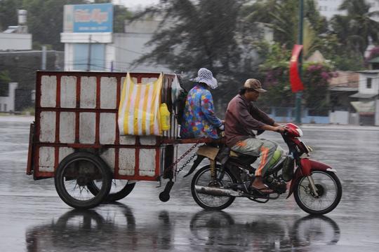 Cơn mưa bất chợt đổ xuống Sài Gòn khiến nhiều người lao động bị ướt mưa nhưng cũng phấn khởi vì không còn phải chịu đựng nắng nóng.