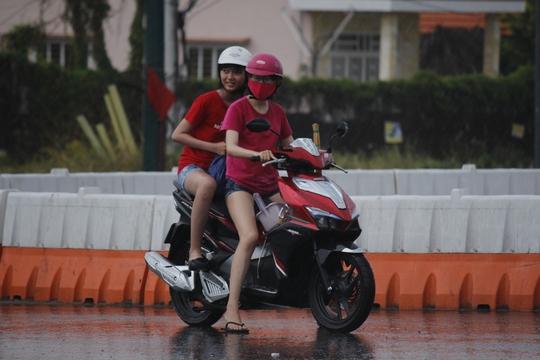 Hai cô gái đứng dưới cơn mưa mà vẫn vui cười thích thú.