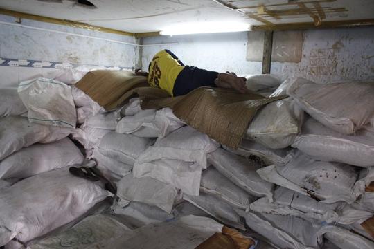 Bên trong kho chứa me, nhân viên dẫm đạp, trải chiếu ngủ trên me nguyên liệu.