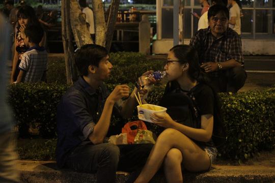 Hai bạn trẻ tranh thủ ăn uống lót dạ trong khi chờ thưởng thức màn bắn pháo bông.