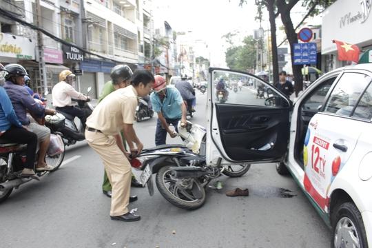 Lực lượng chức năng đang lôi chiếc xe bị mắc kẹt dưới cửa taxi ra ngoài.