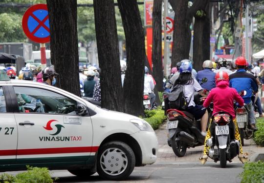 Không chỉ có xe máy, taxi cũng tấp vào vỉa hè chờ bớt kẹt xe để đi tiếp.