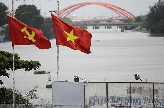 Một công ty nằm cạnh cầu Sài Gòn treo cờ đỏ sao vàng, cờ đỏ búa liềm bay phấp phới, chào mừng ngày lễ Quốc khánh